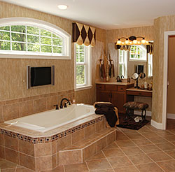 Beautiful tiled bathroom with matching tub, sink and walls.